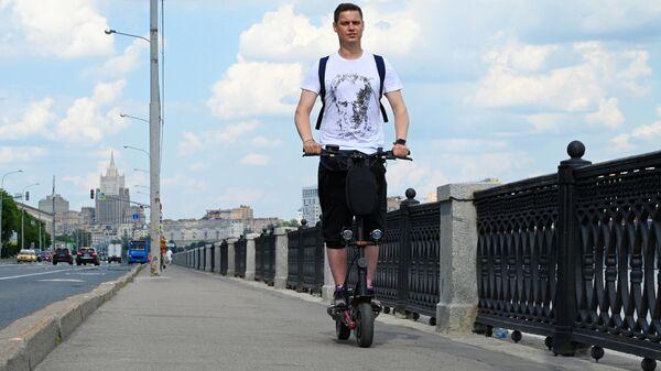 Молодой человек катается на самокате на Бережковской набережной в Москве