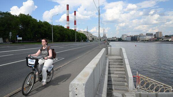 Девушка катается на велосипеде на Бережковской набережной в Москве