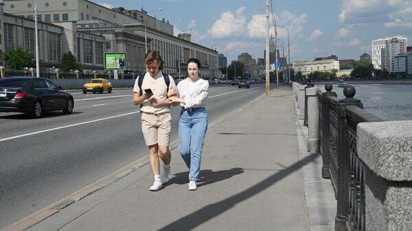 Молодые люди гуляют на Бережковской набережной в Москве