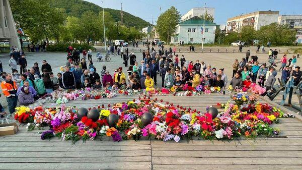 Люди несут цветы, свечи и портреты в память о погибших в авиакатастрофе к стихийному мемориалу на площади Ленина в поселке Палана