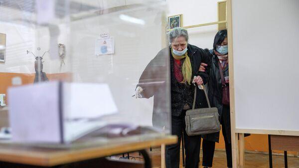 Женщина на избирательном участке в городе Банкя во время парламентских выборов в Болгарии