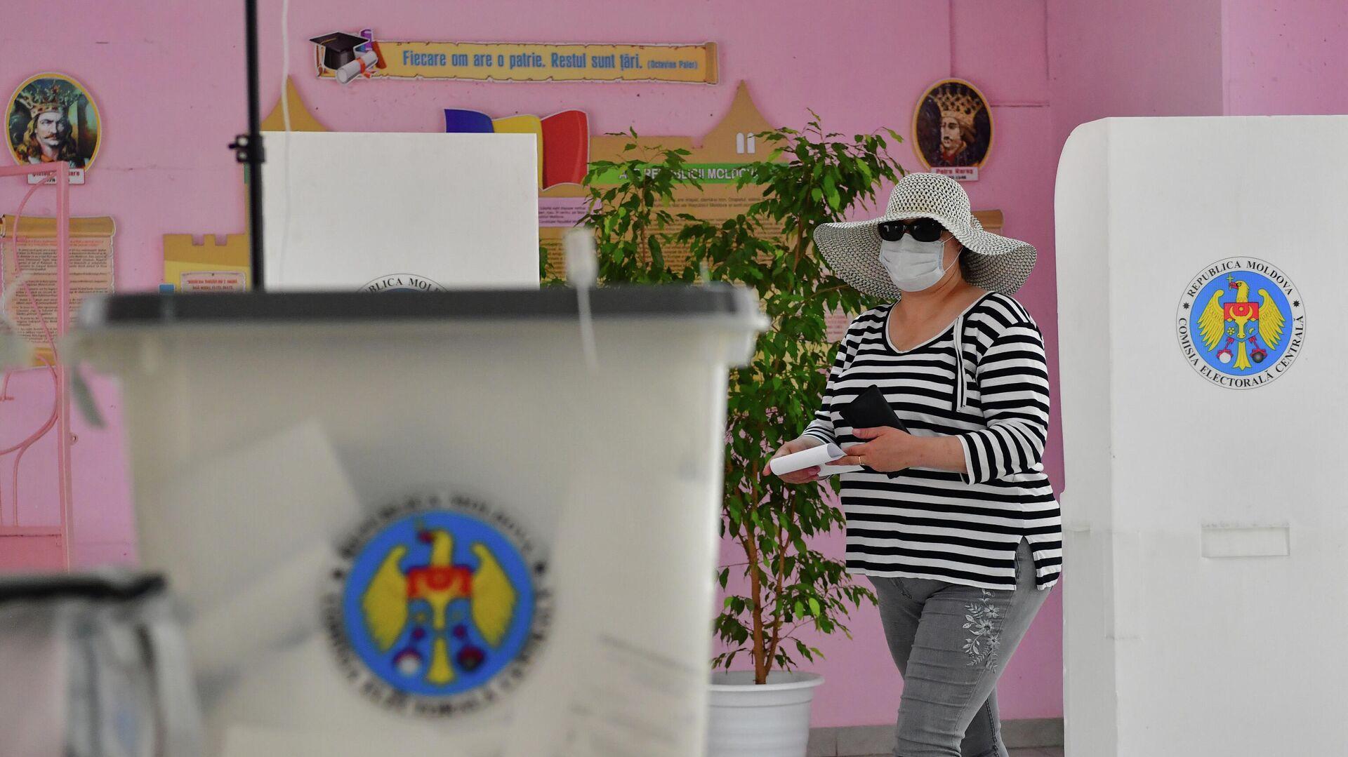 Женщина голосует на избирательном участке в Кишиневе во время досрочных парламентских выборов в Молдавии - РИА Новости, 1920, 12.07.2021