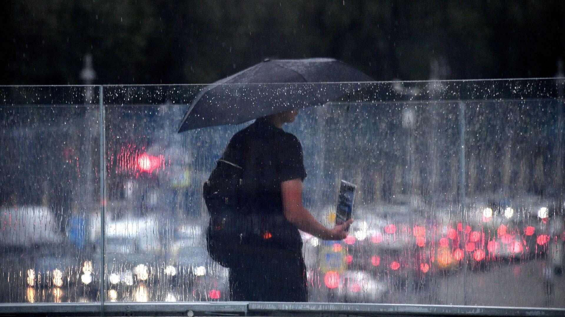 Мужчина под зонтом на одной из улиц в Москве - РИА Новости, 1920, 27.07.2021