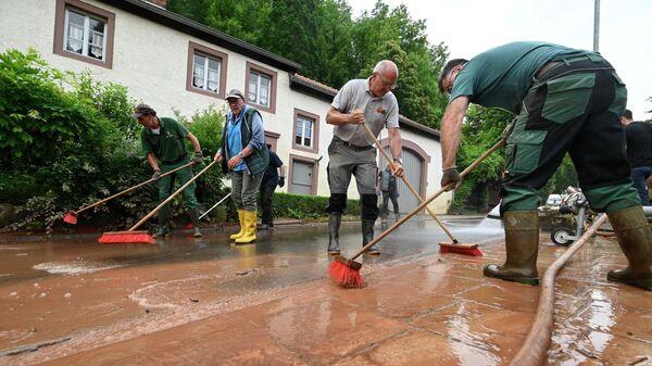 Жители очищают улицу от грязи после наводнения. Бирсдорф-ам-Зее, недалеко от Битбурга, Западная Германия