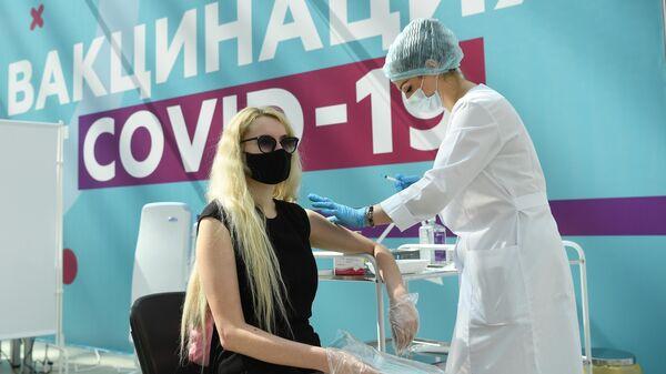 Медицинский сотрудник делает посетителю прививку в центре вакцинации от COVID-19 в Гостином дворе