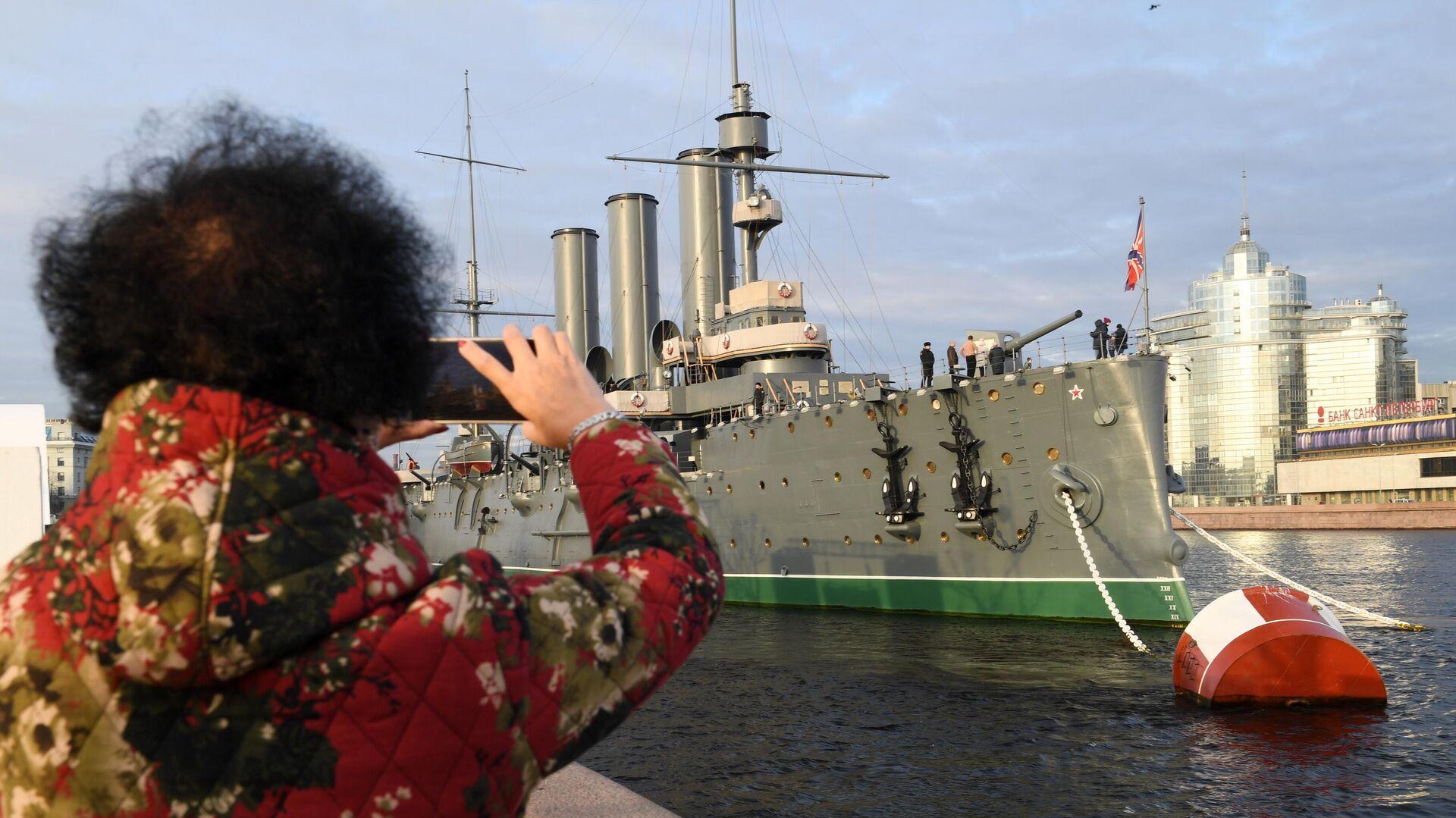 Туристка фотографирует музей Крейсер Аврора в Санкт-Петербурге - РИА Новости, 1920, 20.07.2021