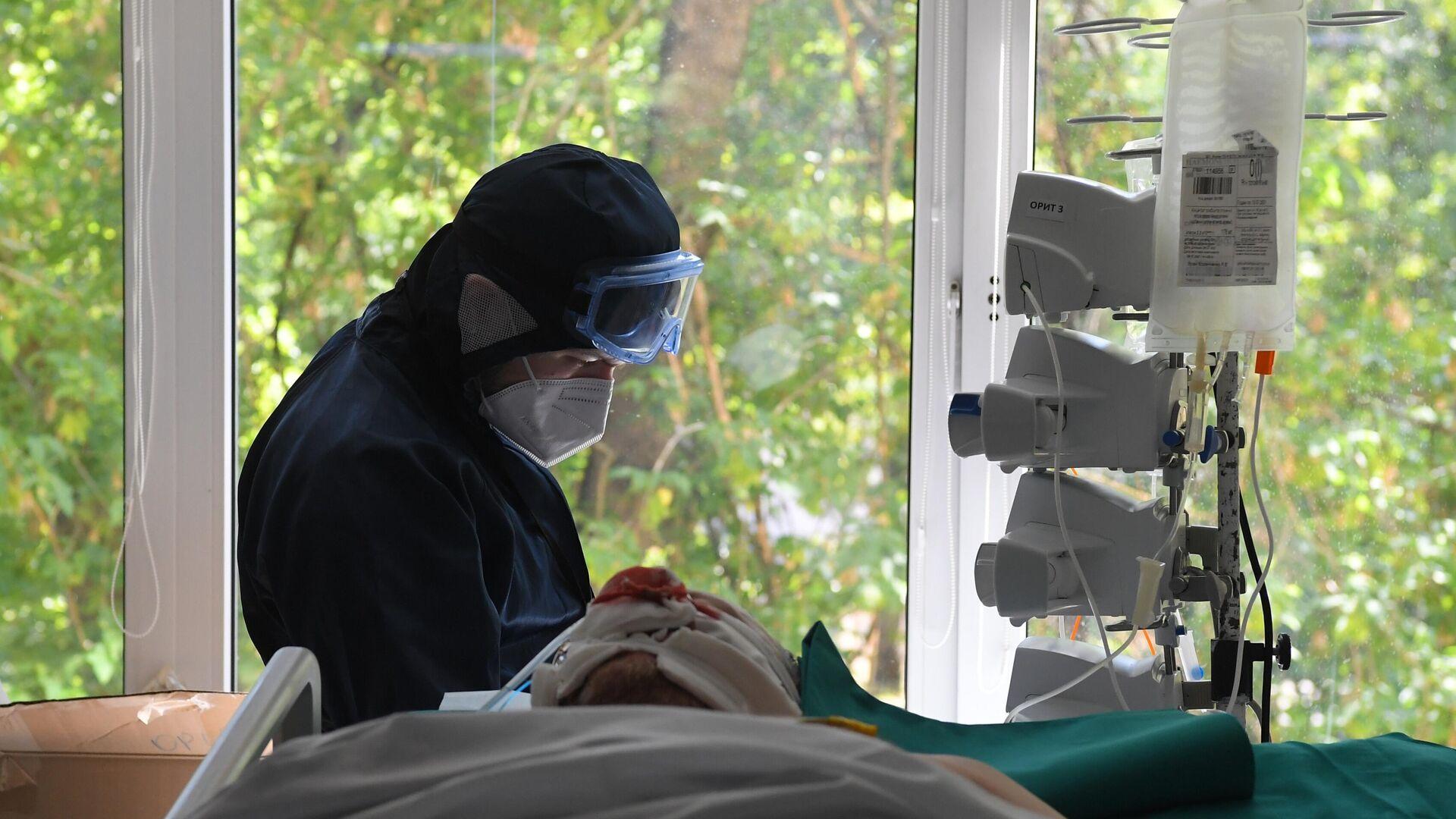 Медицинский работник у постели пациента в отделении реанимации и интенсивной терапии в госпитале COVID-19 в городской клинической больнице № 52 в Москве - РИА Новости, 1920, 29.07.2021