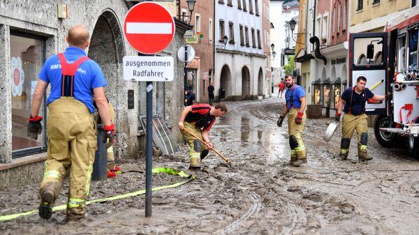 Рабочие очищают улицы от грязи и воды в затопленном историческом центре Халлайна, Австрия
