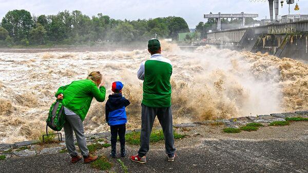 Семья наблюдает за водами реки Инн в Рансхофене, Австрия