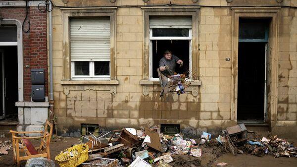 Жилец дома выбрасывает поврежденные предметы из окна после наводнения в Энсивале, Бельгия