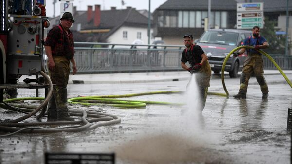 Люди убирают грязь после наводнения в центре города Халлайн, Австрия