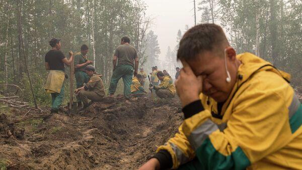 Люди копают траншеи во время тушения лесных пожаров в Якутии