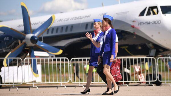 Стюардессы на фоне пассажирского самолета Ил-114-300 на МАКС-2021