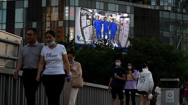 Люди проходят мимо экрана с репортажем о китайских астронавтах во время их первой миссии на китайской космической станции