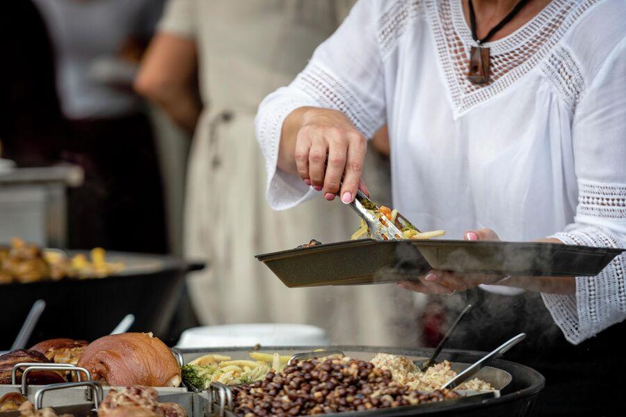 Женщина готовит традиционные блюда Латвии на большой сковороде