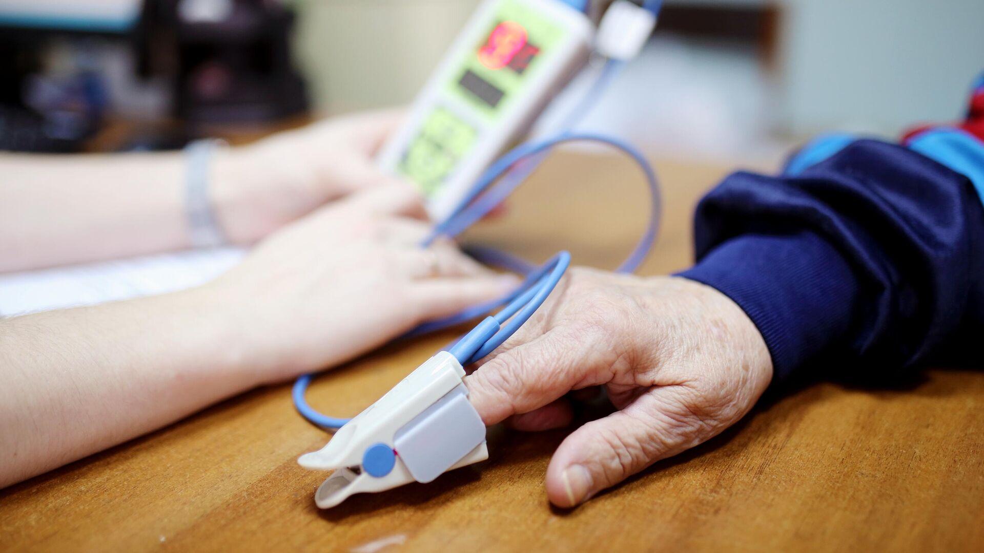 Врач измеряет концентрацию кислорода в крови у пациента, перенесшего коронавирус - РИА Новости, 1920, 03.08.2021