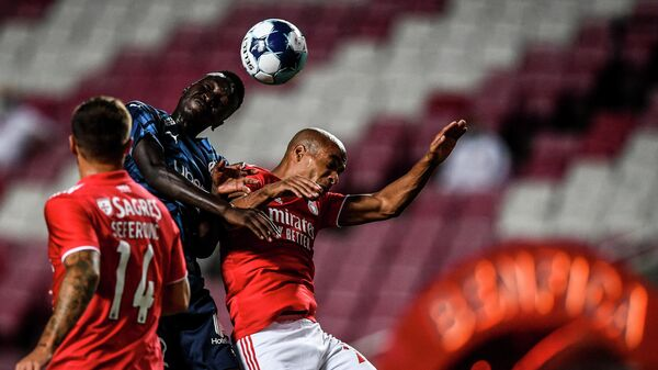 Benfica's Portuguese midfielder Joao Mario (R) heads the ball with Marseille's French midfielder Pape Gueye during an international club friendly football match between SL Benfica and Olympique de Marseille at the Luz stadium in Lisbon on July 25, 2021. (Photo by PATRICIA DE MELO MOREIRA / AFP)