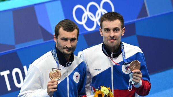 Российские спортсмены, члены сборной России (команда ОКР) по прыжкам в воду Александр Бондарь и Виктор Минибаев, завоевавшие бронзовые медали на соревнованиях по синхронным прыжкам с вышки 10 метров среди мужчин на XXXII Олимпийских играх в Токио.