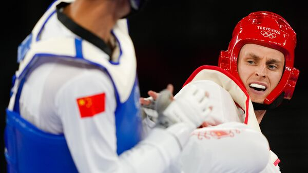 Российский спортсмен, член сборной России (команда ОКР) Владислав Ларин и Сунь Хуни (Китай) в 1/2 финала соревнований по тхэквондо в весовой категории свыше 80 кг среди мужчин на XXXII летних Олимпийских играх в Токио