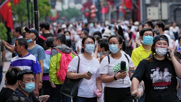 Люди в масках на популярной торговой улице в Пекине