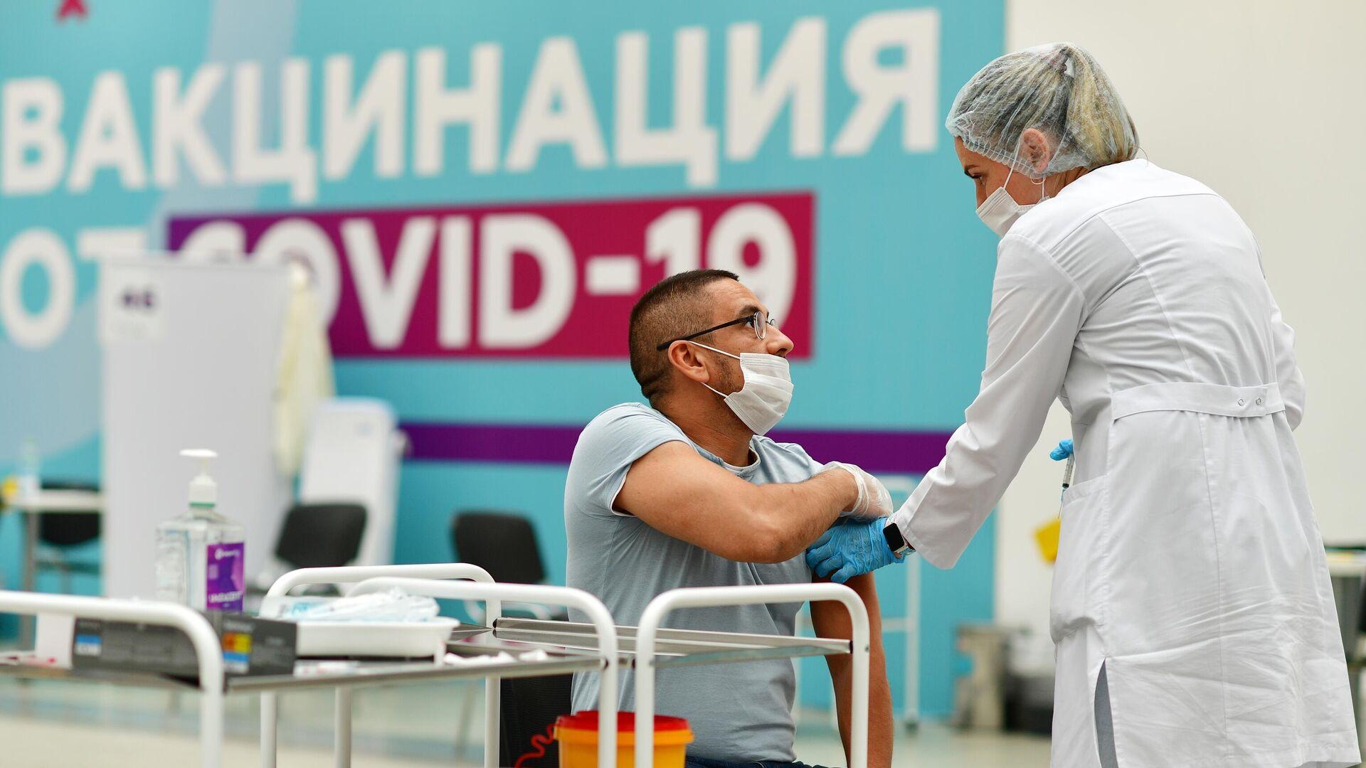 Посетитель делает прививку в центре вакцинации от COVID-19 в Гостином дворе в Москве - РИА Новости, 1920, 30.07.2021
