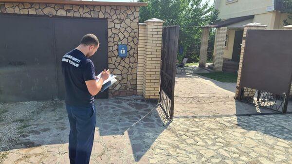 Сотрудник Следственного комитета у дома подозреваемого в убийстве девушки в поселке Петра Дубрава