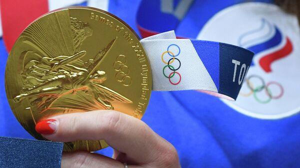Золотая медаль в руке российской спортсменки, члена сборной России Виталины Бацарашкиной