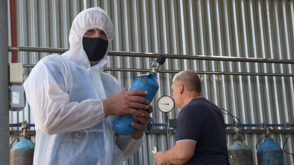 Работники больницы заправляют баллоны с кислородом от автомобильной кислородно-зарядной станции АКЗС-75М на территории Республиканской клинической больницы скорой медицинской помощи во Владикавказе