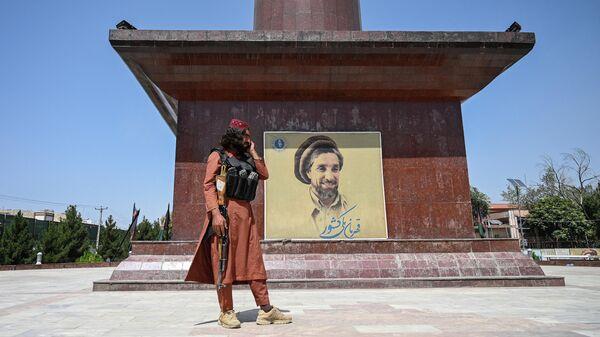 Боевик Талибана* рядом с портретом Ахмада Шаха Масуда в Кабуле