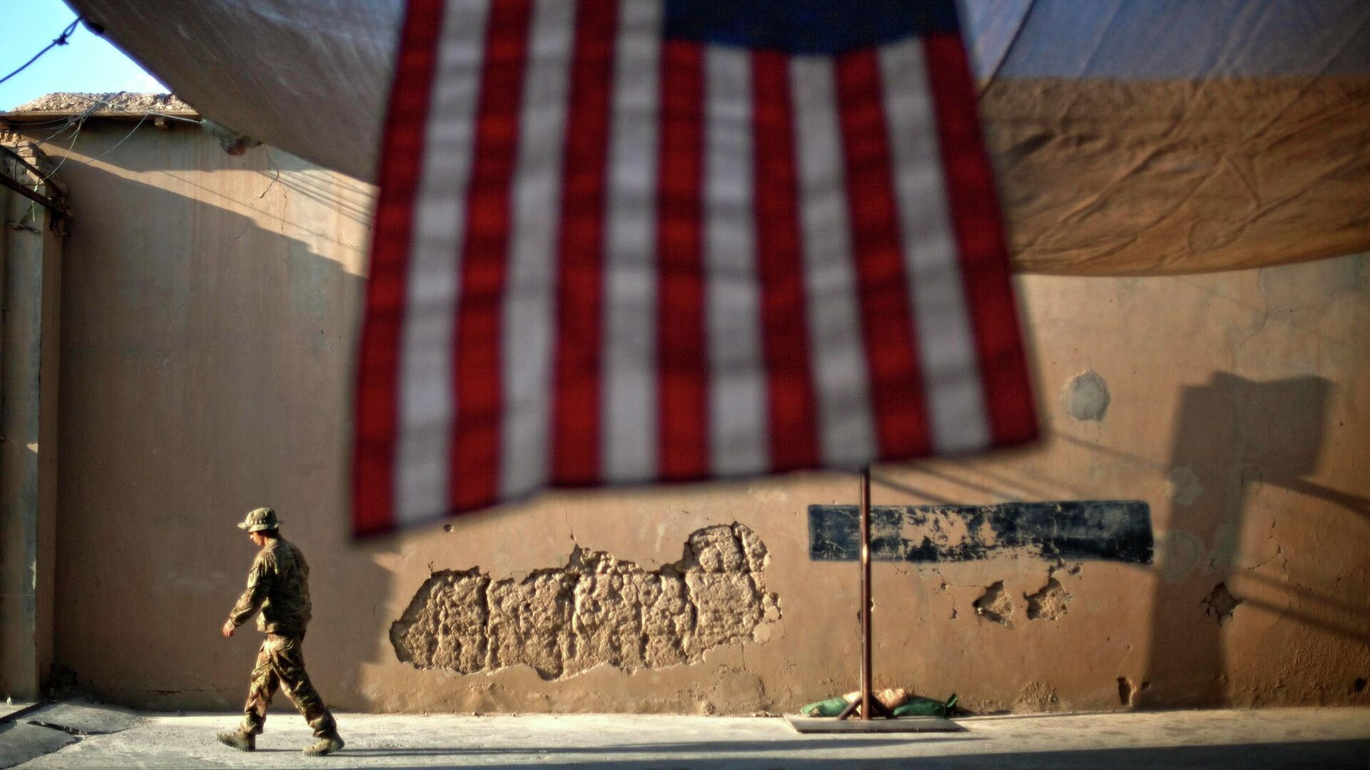 Солдат армии США проходит мимо американского флага на передовой оперативной базе Бостик в афганской провинции Кунар - РИА Новости, 1920, 14.09.2021