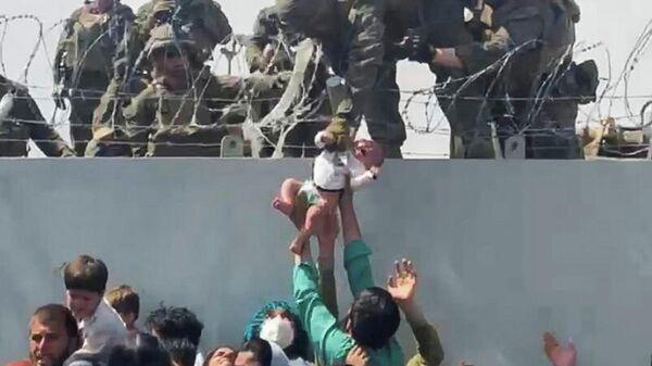 Люди передают ребенка американским военным в аэропорту Кабула
