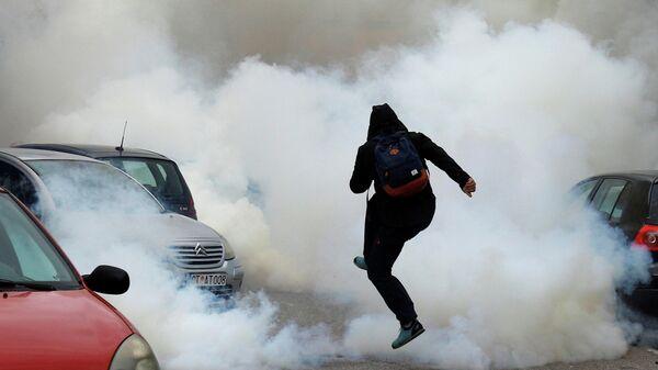 Мужчина в облаке слезоточивого газа во время акции против интронизации епископа Иоаники в Цетинье, Черногория