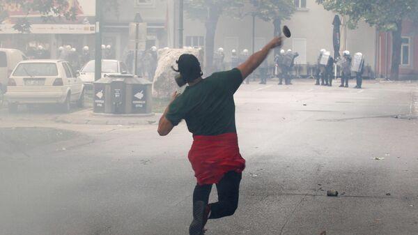 Демонстрант бросает камень во время акции протеста против интронизации митрополита Иоанникия в Цетине, Черногория