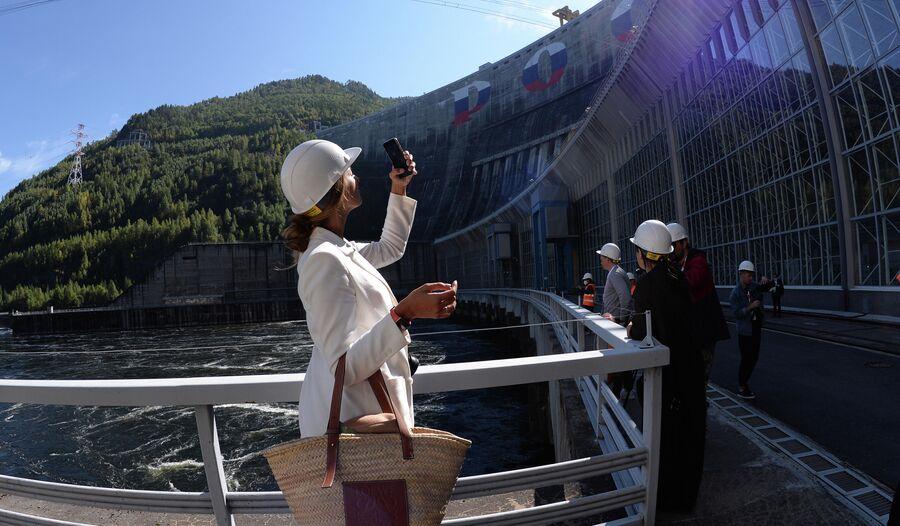 Туристы у здание машинного зала Саяно-Шушенской ГЭС на реке Енисей
