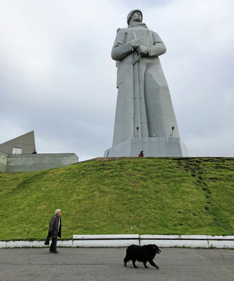 Женщина гуляет с собакой у подножия мемориала защитникам Советского Заполярья в Мурманске, на сопке Зеленый мыс