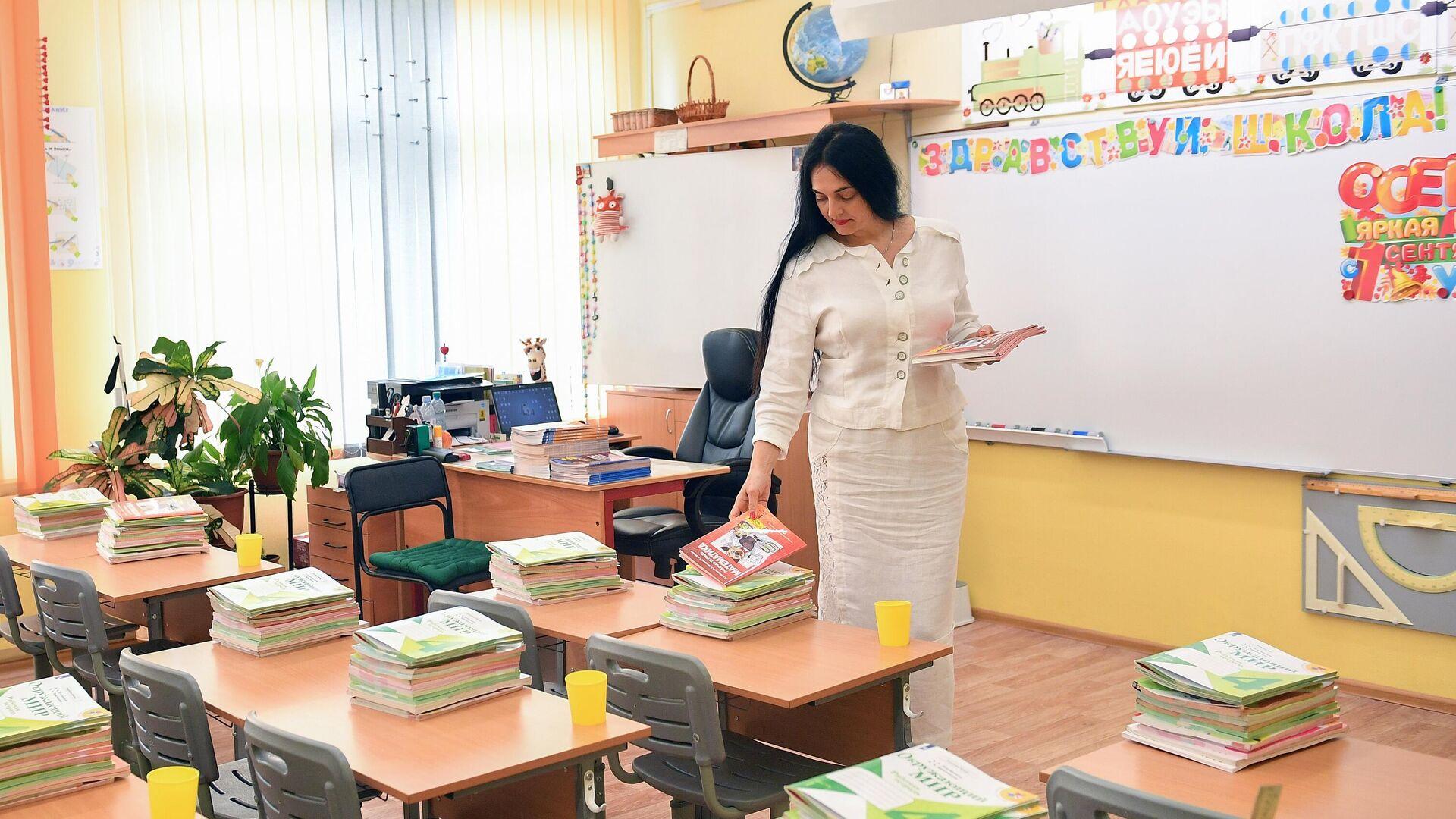 Учитель раскладывает тетради в классе - РИА Новости, 1920, 13.09.2021
