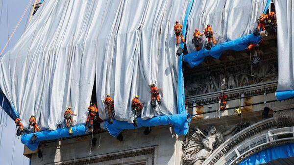 Процесс обертывания Триумфальной арки в Париже по проекту, созданному покойным художником Христо