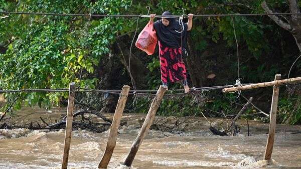 Женщина переходит реку по мосту, уничтоженному наводнением год назад в Сулевеси