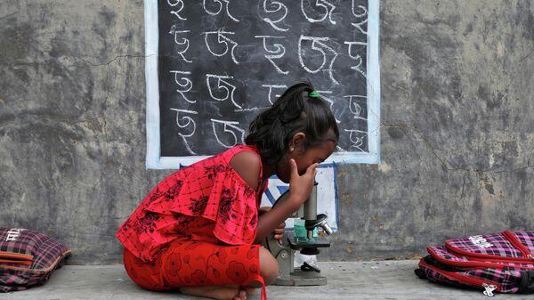 Девочка на уроке под открытым небом после закрытия школ из-за COVID-19, Индия