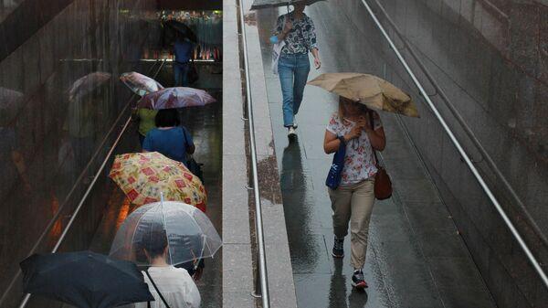 Люди во время дождя на одной из улиц в Москве