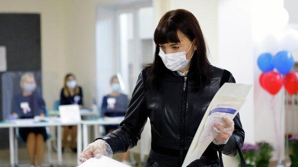 Девушка голосует на избирательном участке No196 в Белгороде