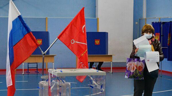 Женщина голосует на избирательном участке в Санкт-Петербурге