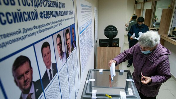 Женщина голосует на выборах депутатов Государственной Думы РФ на избирательном участке №8180 в консульском отделе посольства России в Латвии