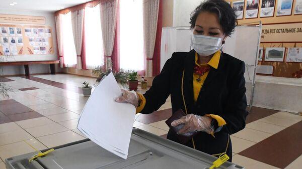 Женщина голосует на избирательном участке №199 на выборах депутатов Государственной Думы РФ в Республике Хакасия
