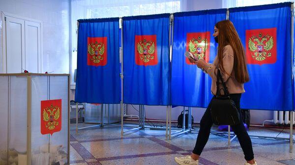 Девушка во время голосования на избирательном участке в Новосибирске
