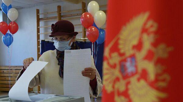Женщина голосует на выборах депутатов Государственной Думы РФ