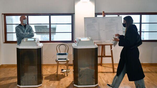 Девушка во время голосования на выборах депутатов Государственной Думы на избирательном участке № 60 в Москве