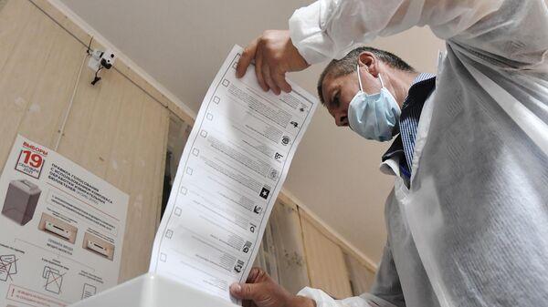 Сотрудник избирательной комиссии подсчитывают бюллетени после закрытия избирательного участка в Севастополе