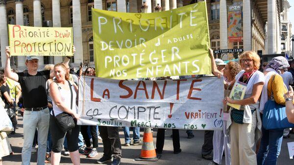 Участники во время протестов против COVID-ограничений в Париже