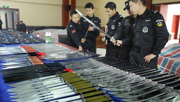 Китайские полицейские рассматривают изъятое оружие. Фото с места событий